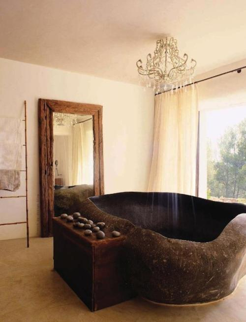 A granite boulder bathtub and a chandelier shower …
