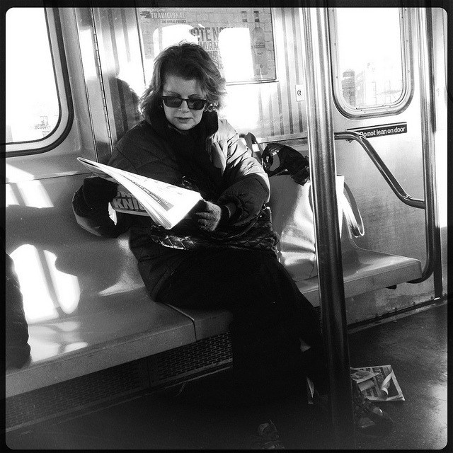 reading the news. on Flickr.Catching up on the morning news on the 7 train.