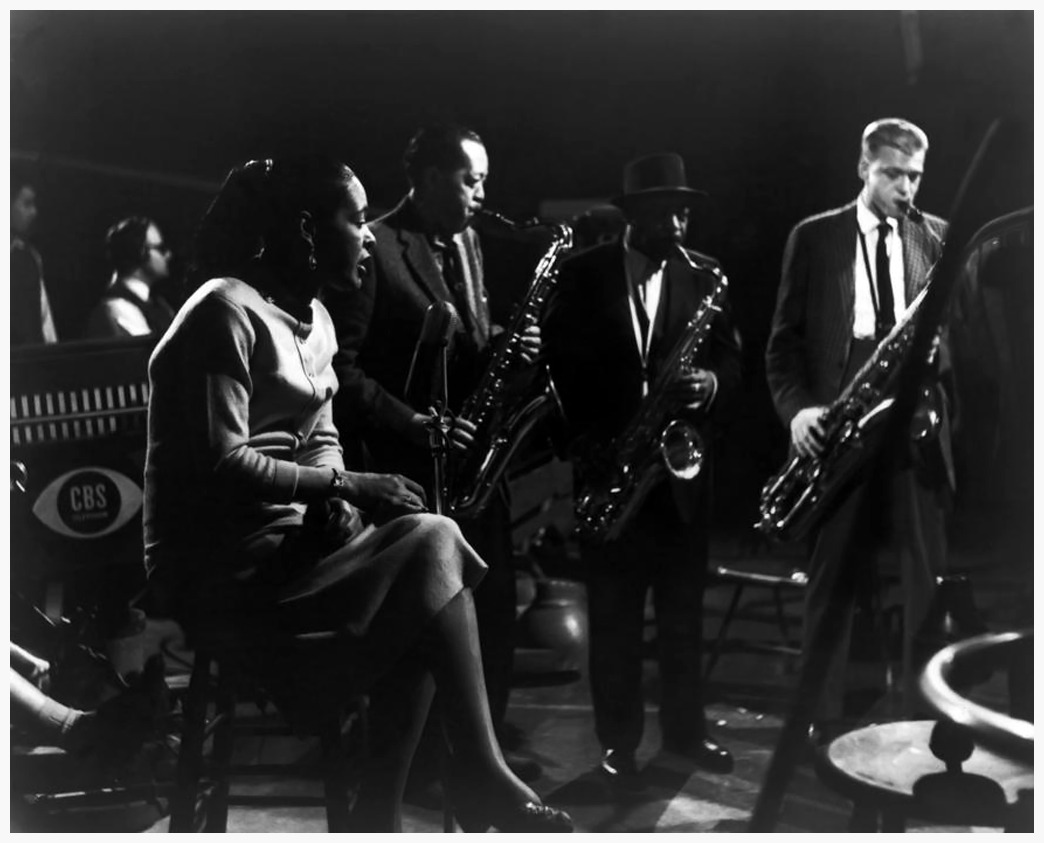 Billie Holiday, Lester Young, Coleman Hawkins and Gerry Mulligan Via the Frank Driggs Collection (Source)