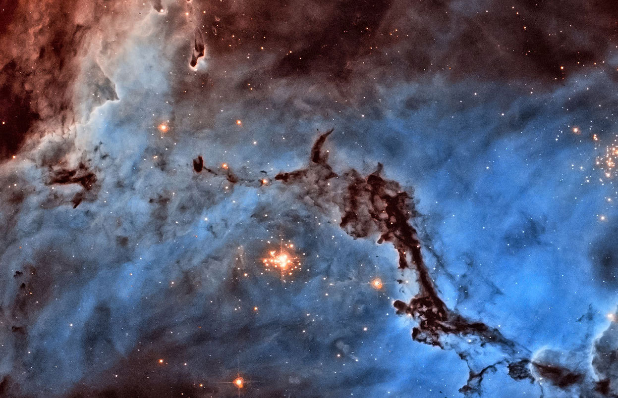 Day 22 of the 2012 Hubble Space Telescope Advent Calendar, one of 25 photos (eventually).  First prize winner of the 2012 Hubble Hidden Treasures competition, image processing category. Josh Lake (USA) submitted this stunning image of NGC 1763, part of the N11 star-forming region in the Large Magellanic Cloud. ESA/Hubble had previously published an image of an area just adjacent to this, based on observations by the same team. Josh took a different approach, producing a bold two-color image which contrasts the light from glowing hydrogen and nitrogen. The image is not in natural colors — hydrogen and nitrogen produce almost indistinguishable shades of red light that our eyes would struggle to tell apart — but Josh's processing separates them out into blue and red, dramatically highlighting the structure of the region. As well as narrowly topping the jury's vote, Josh Lake also won the public vote. (NASA/ESA/Josh Lake)
