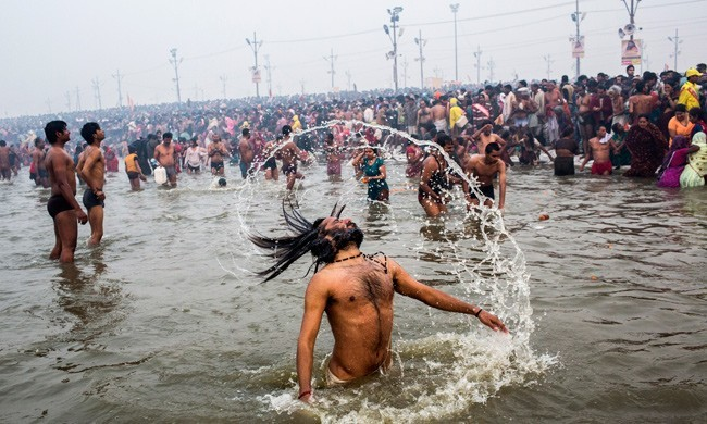 A Hindu devotee flips his hair in the waters of the holy Ganges river during the auspicious bathing day of Makar Sankranti in Allahabad, India. The Maha Kumbh Melad festival is believed to be the largest religious gathering on Earth, attracting more than 100 million people. The festival is held every 12 years on the banks of Sangam, and is celebrated for 55 days.  PHOTO: Daniel Berehulak/Getty Images