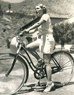 Mary Pickford rides a bike.