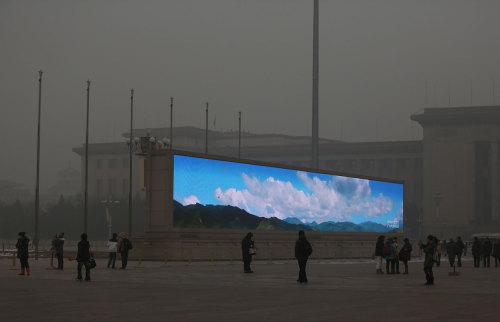 A bright video screen shows images of blue sky on Tiananmen Square during a time of dangerous levels of air pollution, on January 23, 2013 in Beijing. (Feng Li/Getty Images) via The Atlantic