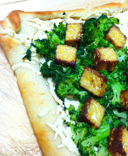 Tempeh Veggie Pizza! Ingredients 2 cups shredded nondairy cheese 1 vegan pizza crust 2 cups chopped broccoli florets, steamed 2 cups chopped arugula 1 1/2 cups cooked and cubed tempeh Instructions Preheat the oven to 450 F. Sprinkle the nondairy cheese over the pizza crust. Spread the broccoli florets evenly over the top, followed by the arugula and cooked tempeh. Baked until the crust is crispy and golden and the cheese is melted, about 8 to 10 minutes.  Enjoy!