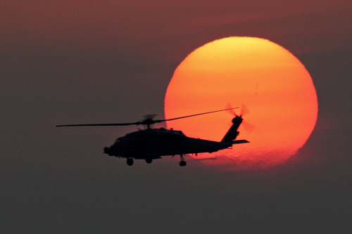 Evening Quickie #soldierporn: You are the nighttime fear… An HH-60H Seahawk helicopter flies over the flight deck of the aircraft carrier USS Dwight D. Eisenhower at sunset in the North Arabian Sea, April 29, 2013. The Eisenhower is deployed to the U.S. 5th Fleet area of responsibility promoting maritime security operations, theater security cooperation efforts and support missions as part of Operation Enduring Freedom.