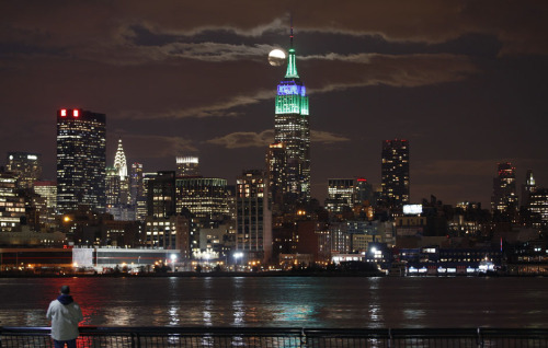 A full moon rises behind the Empire State Building in New York as a man watches in a park along the Hudson River in Hoboken, New Jersey, February 25, 2013.REUTERS/Gary Hershorn