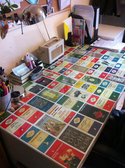 darkdarkstreet:   Our Penguin Classics desk. Makes working from home even better (it's already pretty good: radio, slippers, tea, rat baby cuddles).  I covered a free glass topped desk from my very generous boss at work with over half a box of Penguin covers postcards, a Christmas gift from my girl.                           Your awesome idea has been already stolen, thanks! By me. :P