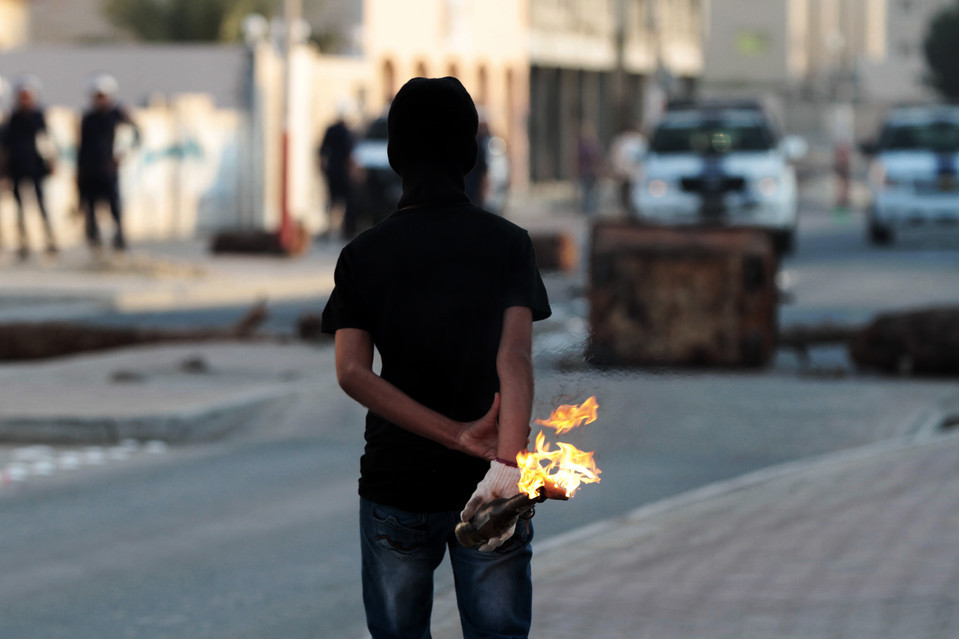 An antigovernment protester prepared to throw a gas bomb at riot police during clashes in the village of Malkiya, Bahrain, Monday. Bahrain's highest court upheld jail sentences against 20 opposition figures convicted of plotting to 'overthrow' the state. Hasan Jamali/Associated Press