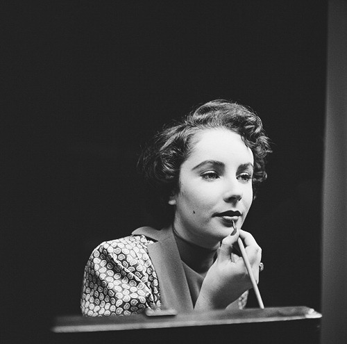 msmildred:  Elizabeth Taylor touches up her lipstick during a stay in London, c. November 1948.