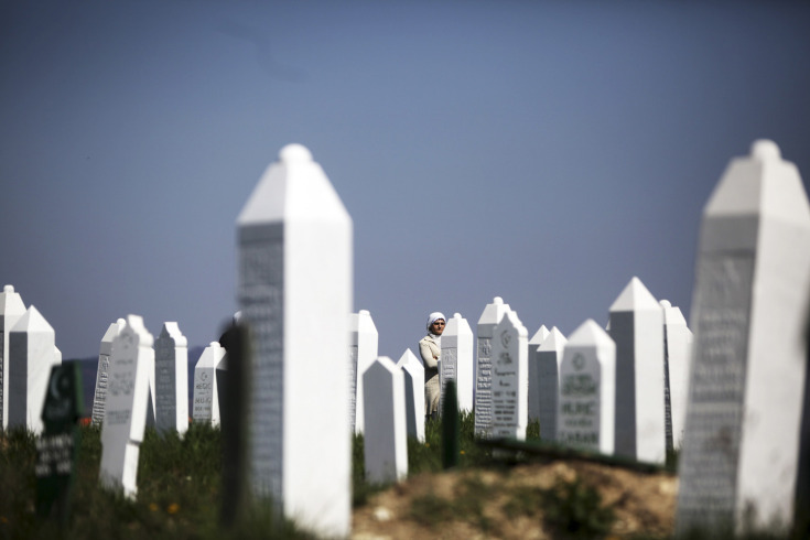 Bosnian Muslim women stand near graves before a mass funeral in the town of Vlasenica, in the Serbian part of Bosnia on April 20, 2013. The remains of some 11 Bosnian Muslims, killed by Serb forces during the country's 1992-1995 Bosnian war, were exhumed from mass graves near Vlasenica with more expected to be found. [Credit : Dado Ruvic/Reuters]