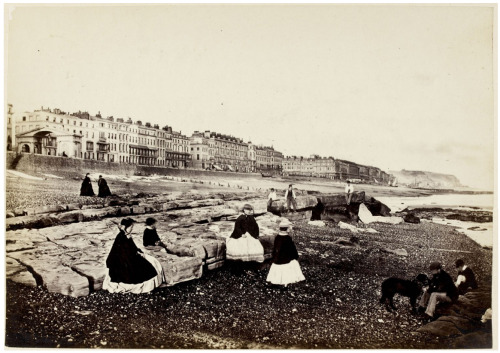 THE GOSSIPING PHOTOGRAPHER AT HASTINGS: SEASIDE PHOTOGRAPHS BY FRANCIS FRITH (1864)  'Hastings from the beach — low water,c.1864' by Francis Frith [BL/ zoomify full-size]  This glimpse of mid-1860s Hastings shows a scattering of ladies and men around on the waterfront. As the British Library entry explains,  The growth of inexpensive rail travel from the mid-19thcentury placed the seaside towns of the south coast within easy reach of the capital. This led to their development as tourist resorts for an increasingly affluent middle class. As Frith noted in his photographic guide book to Hastings and its surroundings: 'We came down from London Bridge in two hours and a half…cheap enough. You face the sea in your drawing-room at St Leonards, and occupy your five bed-rooms at six guineas a week…Whilst Jones has fine open quarters looking landwise for ten shillings a week'. Frith was a pioneer in the field of travel photography, beginning his career with three trips to Egypt and the Holy Land between 1856 and 1860. In 1859 he founded his own publishing firm in Reigate, Surrey, which issued albums and postcards of views throughout Britain. The firm became the largest of its kind in the 19th century, continuing to be run as a family business until 1971.  For more about Frith's seaside photographs, including a copy of his 1864The Gossiping Photographer at Hastings, see the British Library.