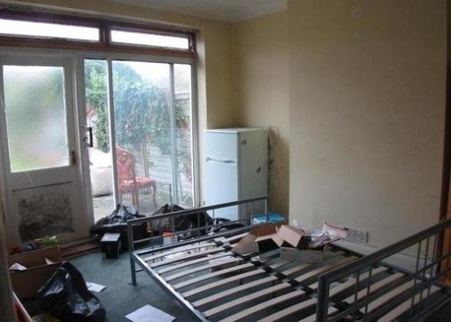 In this example, clever positioning of furniture, white goods and refuse has made a small room look even more squalid and unhygenic than it otherwise would have. The positioning of an upholstered dining chair in the garden, and a bed in what appears to be the kitchen, adds nicely to the sense of chaos.