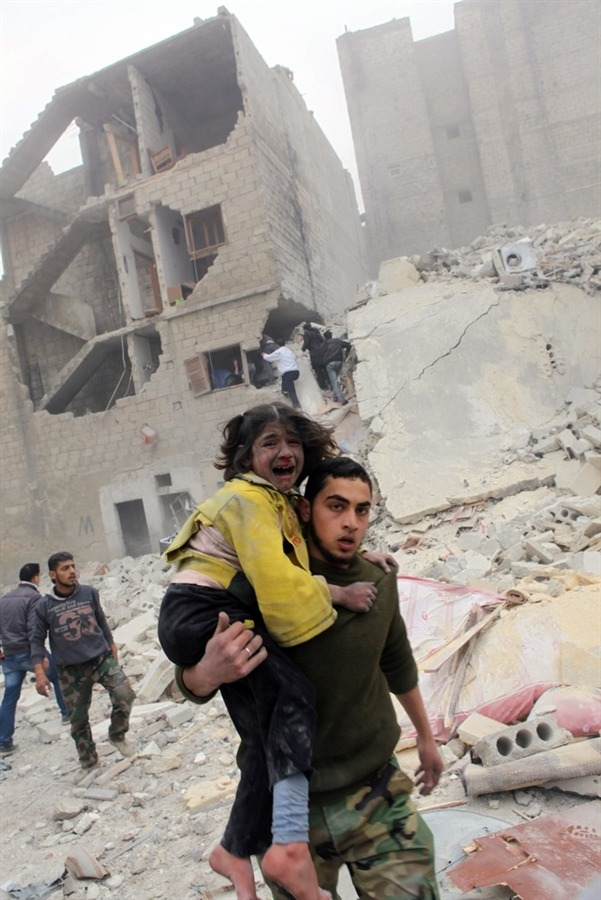 A man holds a child in his arms after an airstrike in Aleppo, Syria, on Feb. 3, 2013. Photo by Thomas Rassloff / EPA