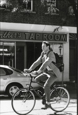Kevin Kline rides a bike. Down Main Street in Northport, N.Y.