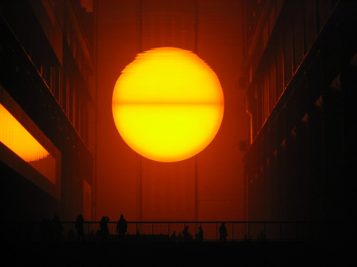 "likeafieldmouse:  Olafur Eliasson - The Weather Project (2003) ""Representations of the sun and sky dominate the expanse of Turbine Hall. A fine mist permeates the space, as if creeping in from the environment outside. Throughout the day, the mist accumulates into faint, cloud-like formations, before dissipating across the space.  At the far end of the hall is a giant semi-circular form made of hundreds of mono-frequency lamps.  Generally used in street lighting, mono-frequency lamps emit light at such a narrow frequency that colors other than yellow and black are invisible, thus transforming the visual field around the sun into a vast duotone landscape."""
