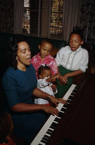 vintageblackglamour:  Happy Mother's Day! Here is Coretta Scott King singing and playing the piano with her children Yolanda, Martin III, Dexter (left corner) and Bernice at home after church in November 1964. Photo: Flip Schulke/Corbis.