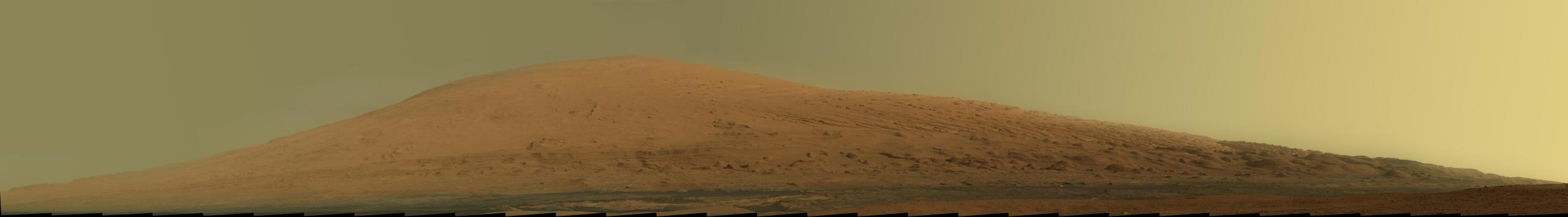 "Mount Sharp Panorama This mosaic of images from the Mast Camera (Mastcam) on NASA's Mars rover Curiosity shows Mount Sharp in raw color  as recorded by the camera. Raw color shows the scene's colors as they would look in a typical smart-phone camera photo, before any adjustment. [White-balancing version can be found here.] Mount Sharp, also called Aeolis Mons, is a layered mound in the center of Mars' Gale Crater, rising more than 3 miles (5 kilometers) above the crater floor, where Curiosity has been working since the rover's landing in August 2012. Lower slopes of Mount Sharp are the major destination for the mission, though the rover will first spend many more weeks around a location called ""Yellowknife Bay,"" where it has found evidence of a past environment favorable for microbial life. This mosaic was assembled from dozens of images from the 100-millimeter-focal-length telephoto lens camera mounted on the right side of the Mastcam instrument. The component images were taken during the 45th Martian day, or sol, of Curiosity's mission on Mars (Sept. 20, 2012). The sky has been filled out by extrapolating color and brightness information from the portions of the sky that were captured in images of the terrain."