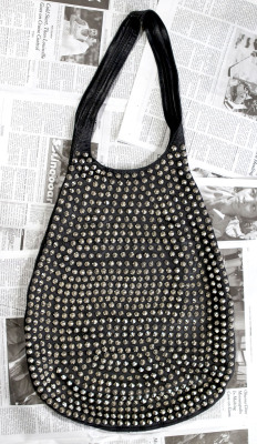 bagavond:   Leather studded hobo  Designer: Tom Binns known more for his unusual jewelry. Jennifer's closet is chock-full of amazing bags like this edgy studded hobo which has this free flowing shape more like an oversized sack. It has all the signs of a well loved bag from everyday use, yet still looks perfectly in tact. What makes this thing so magical is this simple flat construction with innumerable amount of studs on both sides.