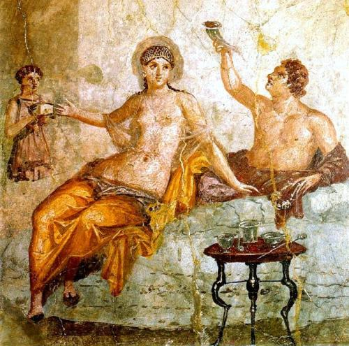 ancientart:  Banquet scene, fresco from Herculaneum, Pompeii style IV (50-79 AD).  This fresco from a house in Herculaneum contains something strange: The small woman on the left appears to have no legs. On closer look, we notice that a lever appears to be mounted within the right arm of the figure, moving in a slit up and down. Possibly a kind of club is attached to this lever, beating against the box held by the figure. There is also a slot at the bottom of the figure, part of something that looks like a drawer extruding from the figure. To the bottom right of the figure there is a straight line, which may indicate that it is standing in or mounted on a niche. Given the proportions, the slot at the bottom, the missing legs, and the lever, it seems natural to assume that this is a mechanical device, possibly a clock, and not a human being.  Courtesy & currently located at the National Archaeological Museum of Naples. Via Wiki Commons
