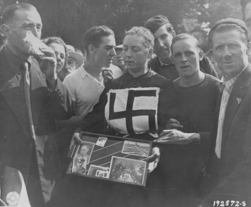Members of the French resistance and citizens of Laval publicly humiliate a woman who consorted with a German officer during the occupation. Her hair has been shorn and she has been marked with a swastika. In addition, she is forced to display photographs of the German with whom she had a relationship.