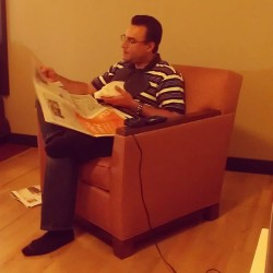 Classic Dad: reading the newspaper, sitting in a comfy chair, a bib tucked into his shirt, and eating snacks #dad #daddy #funny #thisisnormal #normal #haha #newspaper #reading #comfychair #bib #eatingsnacks #munchies (at Red Roof Inn)