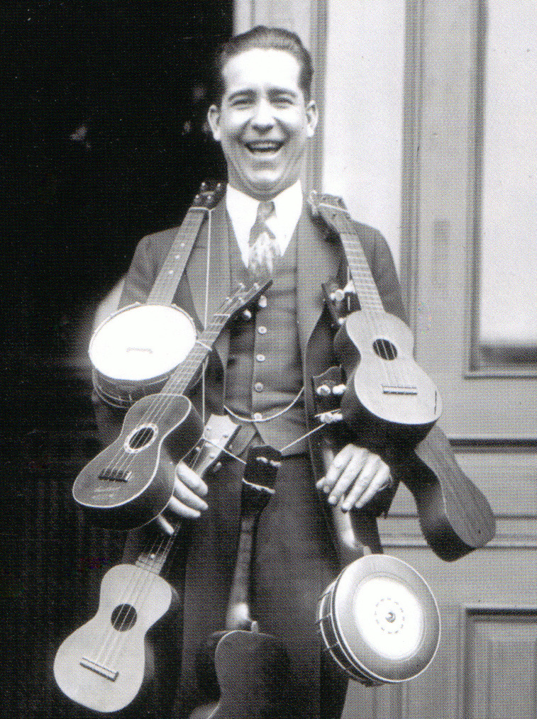 Festooned with Ukuleles Johnny Marvin proudly displays his ukulele collection. According to his wife, Johnny wears the ukes every day except Thursdays.