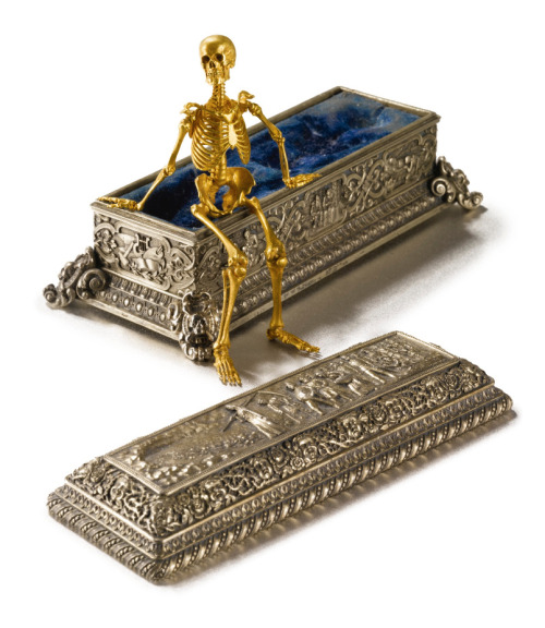 'THE ROUCHOMOVSKY SKELETON':  A RUSSIAN GOLD ARTICULATED SKELETON IN SILVER-GILT SARCOPHAGUS Estimate: 150,000 - 250,000 USD  The fully articulated human skeleton in a velvet-lined coffin chased around on each side with three panels showing the course of life, one end with attributes of the arts, the other with attributes of war,  the removable cover with the journey in the footsteps of the Angel of Death, surrounded by the faces of infants alternately laughing and crying. Skeleton signed in Cyrillic, on the right splint-bone: Mozyr [18]92 Odessa [18]96 and on the left splint-bone Rouchomovsky; Sarcophagus signed on lid: Israel Rouchomovsky and in Cyrillic on base Israel Rouchomovsky Odessa 1901. Length of skeleton 3 1/2 in., length of coffin 4 3/8 in. 9 cm; 11.2 cm The skeleton 1892-1896, the sarcophagus 1896-1906 Israel Rouchomovsky, Mozyr and Odessa,   (Source: Sotheby's) If only I had a spare small fortune lying around…*sigh*