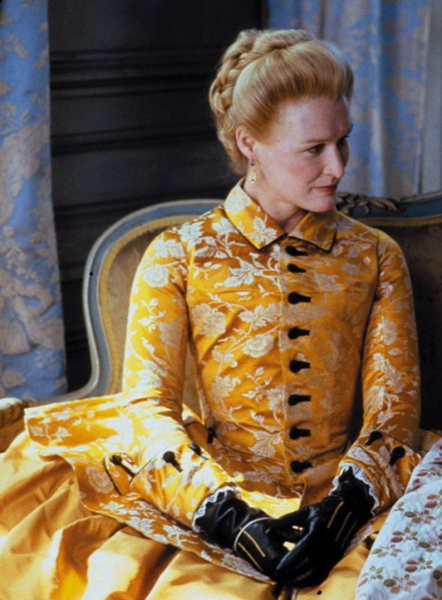 Dangerous Liaisons - Glenn Close as Marquise Isabelle de Merteuil wearing a yellow taffeta gown with full skirt and brocade jacket with black buttons. Her black leather gloves had yellow details. The costumes were designed by James Acheson.