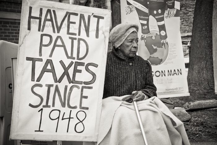 Tax resistance. Juanita Nelson sits with a sign outside of the Main Street Post Office in Brattleboro on Tax Day during a informational picket on tax resistance.(Zachary P. Stephens/Brattleboro Reformer)