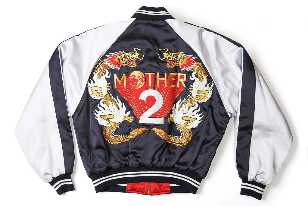 tinycartridge:  Satoru Iwata's killer Mother 2/Earthbound jacket Before we get into this amazing piece, here's a real quick follow-up to yesterday's Japanese Mother 2 interview — someone's translating it! They're translating the interview, that is, not localizing the Wii U Virtual Console release. Just want to make that clear. Anyway, Nintendo's CEO and president tweeted this photo last night of a special gift he (and the rest of the Mother 2 team) received after working on the RPG. As you can imagine, this is an extremely rare item, but one actually showed up in an online auction a few years ago! I'm envisioning Iwata spending the evening cruising through Shinjuku streets, wearing this jacket and a pair of leather gloves to complete the Ryan Gosling/Drive image. Iwata's giving you a night call to tell you how he feels. BUY Mother 3/Earthbound, Hobonichi Techo 2013