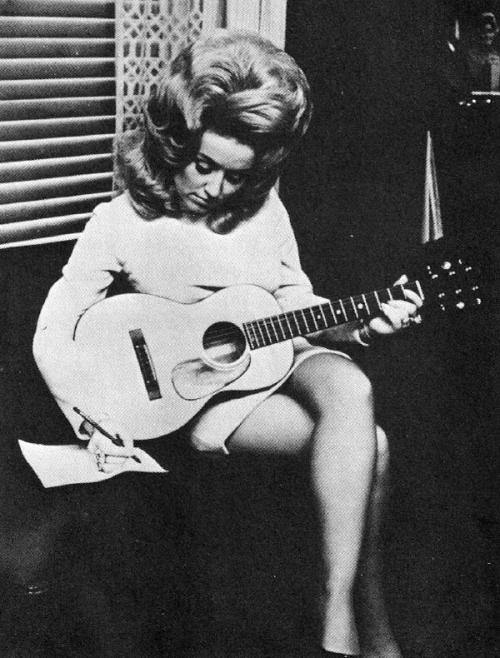 "books0977:  Young Dolly Parton sitting with a guitar writing a song. 1960s. Parton wrote every day, and had more than a 100 songs at her disposal. A multi-instrumentalist, Parton was more than equipped to accompany herself. She wrote the traditional country songs about cheating, but there was also the feminist anthem ""Just Because I'm a Woman,"" which proclaimed ""My mistakes are no worse than yours, just because I'm a woman."""