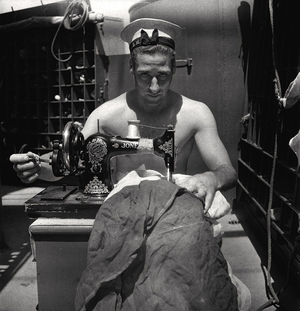 Cecil Beaton - a Royal Navy sailor on board HMS Alcantara uses a portable sewing machine to repair a signal flag during a voyage to Sierra Leone, March 1942
