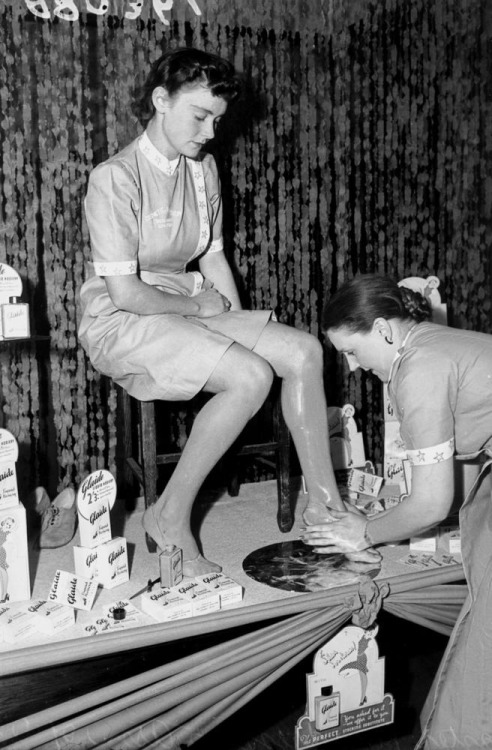 Young lady having liquid hosiery applied to her legs in a store, Brisbane, September 1941 (by State Library of Queensland, Australia)