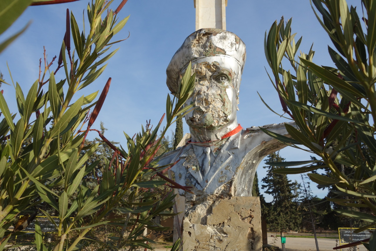 Hafez al-Assad, After a Fall. Bust of Mr. Assad, on the parade ground of the military school at al-Muslimiyah.  Pilot. Military officer. Commander of Syria's Air Force. Defense Minister. Coup organizer. Prime Minister. President. Father of current president. A man whose clique put his portrait on Syria's currency. And here, defaced. ABOUT THE PHOTOGRAPH By the author. Muslimiyah, a short drive north of Aleppo. A few days ago. Syria.