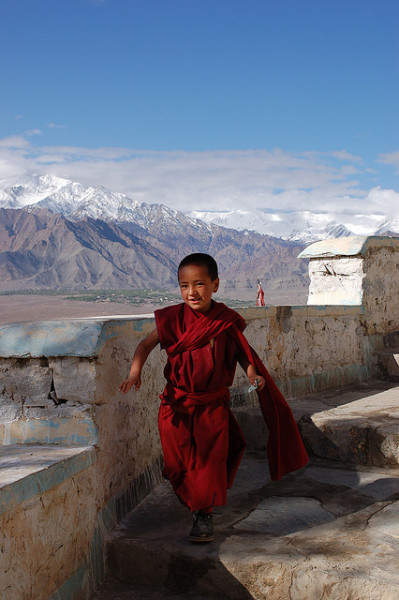 uncommonjones:  Monk and Mountains by emilie.richer on Flickr. Photographer's Note: Thiksey Monastery, Ladakh, India: A novice monk runs down from morning prayers after receiving his allowance