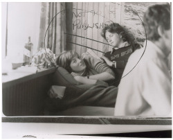 """Uncommon early 10 x 8 glossy news photo of a young Diana lying in bed, with a young man seated behind her, and a bottle of Johnnie Walker sitting on the window sill. Stamped February 1981 on back, the image is clear. The image has crop lines and 'Not to be published' handwritten on the front. Note on back, otherwise light wear. A super early image quite possibly never seen by the public. RR Auction COA."""