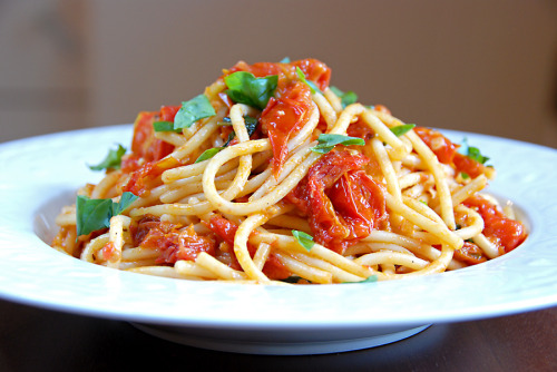 iwanttoeatfood:  Spaghetti with Roasted Tomatoes serves 2-3 1 pound spaghetti pasta water (do not drain the pasta) 3 packages of cherry tomatoes (approximately 25-30 tomatoes) 1/3 cup italian bread crumbs 4-5 garlic cloves, 1/2 minced, 1/2 sliced 1 tsp red pepper flakes  (more if you like a little kick) 1/2 cup dry white wine 1 tbsp butter (optional) 4 tbsp olive oil basil leaves (1/2 a bunch) parmigiano reggiano cheese salt & pepper  Preheat the oven to 325 degrees.  Half the cherry tomatoes and place in a large bowl.  Add salt, pepper, breadcrumbs and 2 tbsp of olive oil.  Place on a large baking sheet (either spray with cooking spray or use parchment paper) in a single layer and bake for 60 minutes. In a large skillet heat 2 tbsp olive oil and butter over low heat.  Add the garlic and red pepper flakes and cook for 1 minute.  Add white wine and simmer for 3-4 minutes.  Add 6-8 large, whole basil leaves.  Turn off heat. When tomatoes are 3/4 done, remove about 15 tomato halves from the oven and add them to the wine mixture.  Smash them gently with the back of the spoon.  Turn the heat back on and cook the tomatoes in the wine mixture for a few minutes.  When the rest of the tomatoes are done add them to the skillet.  When the spaghetti is almost fully cooked (still al dente) add to the skillet.  I use thongs for this.  It is perfectly fine to bring along whatever pasta water is on the noodles.  Also add 3 ladles of the pasta water to the pasta and wine mixture.  Stir to combine over low heat for 1-2 minutes.  Turn off the heat, add a few fistfuls of cheese to the pasta as well as a ton of torn basil leaves.