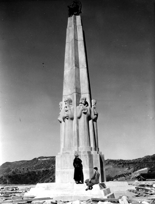 Women visiting the Astronomer's Monument at a still unfinished Griffith Observatory, 1930's. The Hollywoodland sign can be seen in the background.