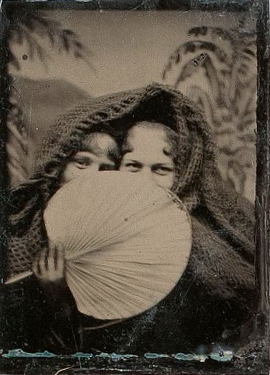 ca. 1870-1900's, [tintype portrait of two cloaked ladies smiling demurely from behind a palm fan] via Cowan's Auctions
