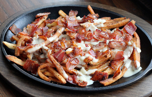 prettygirlfood:  Bacon & Blue Cheese Fries Ingredients: 2 whole potatoes, cleaned, and peeled 3 slices of Nueskes bacon (or your favorite), cooked, and chopped 1/4 cup shallot, finely diced 2 cloves garlic, diced 1 tbsp unsalted butter 1 cup of blue cheese, crumbled 1/2 cup of milk 1 tsp cracked black pepper 3 cups canola oil Salt and pepper to taste Start by cutting your potatoes in half, lengthwise. Then cut them into about 1/2 inch slices, lengthwise. Place them on their side, and slice in 1/2 slices again until you have a french fry cut. See the picture below, or do a quick Google search to see how it's done. Place your cut french fries into a large bowl of cold water as this will help remove some of the starch as well as prevent the potatoes from turning brown.  To medium size pot, add the canola oil and bring it up to 325 degrees. While the oil preheat, drain the potatoes and lay them out on a towel. Gently pat them to dry as you do not want wet potatoes to go into the hot oil. When the oil has reached temperature, add a small handful of potatoes to the oil, and cook them for about 4 minutes. After 4 minutes, remove them with your kitchen spider or slotted spoon and set them on a paper lined baking sheet to drain any excess oil. Repeat with remaining potatoes, making sure you bring the oil temperature up to 325 degrees after every batch. During this time, let's go ahead and make the blue cheese sauce. To make the sauce, add the butter to a skillet and let it melt over medium heat. Toss in the shallots and garlic, and give that a good mix. Let this sweat down for about 4 minutes. Add in the blue cheese, milk, and black pepper. Raise the heat a bit and let this begin to melt down and become nice and bubbly. Stir along the way. Once the sauce thickens, reduce the heat to low, or remove from the heat and set aside. Once all of your potatoes have cooked, raise the temperature of your oil to 375 degrees. Again, in small batches, add the precooked potatoes back into the oil, and cooked until golden brown, roughly 4 minutes. Again, remove with your spider, however toss in a paper lined bowl. Season with salt and pepper. Repeat with remaining potatoes. After the french fries are complete, it is then time to assemble. Preheat your oven broiler to 450 degrees. Add a bundle of french fries to a baking dish. I used my good 'ol cast iron fajita skillet, spoon a bunch of the blue cheese sauce all over the fries, and top with the chopped bacon. Place under the broiler until the cheese is nice and bubbly, roughly 4-5 minutes. Your end result is an awesome flavor combination of smoky bacon and blue cheese. Pair that with these amazing homemade french fries, and well in baseball terms, you just hit a homerun. Perfect for any side dish, and heck pair these up with a classic burger, and you've just impressed not only yourself, but those around you. Hope you enjoy.