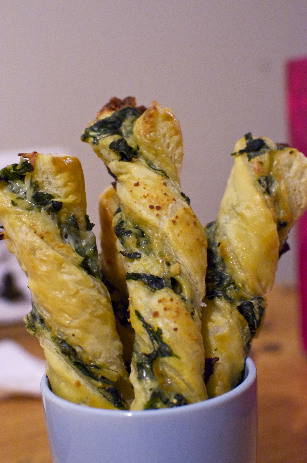 Spinach and Artichoke Cheese Twists Join me on my countdown to the Super Bowl! Come back everyday for a new recipe that you can enjoy while watching the biggest football game of the year!            Countdown to the Super Bowl                         [[MORE]]    5 more days! Spinach and Artichoke Cheese Twists  Spinach and artichoke dip is a classic appetizer for the Super Bowl, so why not combine it with cheese twists? Not only are these cheese twists tasty, but they can be made in advanced to help make the big day less stressful!   You and your party guests will love these cheese twists! They are buttery, cheesy, flaky, and filled with creamy spinach and artichoke filling. These will make for the perfect appetizer to any party!   Spinach and Artichoke Cheese Twists 1/3 cup frozen chopped spinach, thawed 1/2 cup chopped artichoke hearts 3 oz cream cheese, softened 1/4 cup grated parmesan cheese, divided Pinch garlic salt 1 egg 1 tbsp water 1 package puff pastry, thawed Flour, for dusting 3/4 cup grated mozzarella cheese — Preheat the oven to 400 degrees F. Line a large baking sheet with parchment or wax paper. In a medium bowl, combine the spinach, artichoke hearts, cream cheese, 3 tbsp parmesan cheese, and garlic salt.  In a small bowl, whisk together the egg and water to create an egg wash. On a floured surface, unfold one sheet of puff pastry. Brush a little egg wash on top. Sprinkle half of the mozzarella cheese evenly on the puff pastry, then evenly spread the spinach and artichoke mixture on top. Sprinkle the remaining mozzarella cheese on top of the spinach and artichoke mixture.  Unfold the other puff pastry sheet and brush with egg wash. Flip this sheet of puff pastry over onto the mozzarella cheese so that the egg washed side is touching the cheese. Press down on the sheet with your fingers to compress the layers together.  Cut the sheet in half lengthwise, then cut into strips of about 3/4 inch in width. Grab both ends of each strip, twist in opposite directions to form a spiral, and place on the prepared baking sheet.  Brush each cheese twist with egg wash and sprinkle the remaining 1 tbsp parmesan cheese on top. Bake at 400 degrees F for about 20 minutes, or until golden brown. Makes about 20 cheese twists. ***Note: To prepare ahead of time, make the twists, arrange on the baking sheet in advanced, and store in the refrigerator, making sure to keep the baking sheet tightly wrapped with plastic wrap. On the day of the party, unwrap, brush with egg wash, sprinkle with parmesan cheese and bake at 400 degrees for 20 to 25 minutes, or until golden brown.