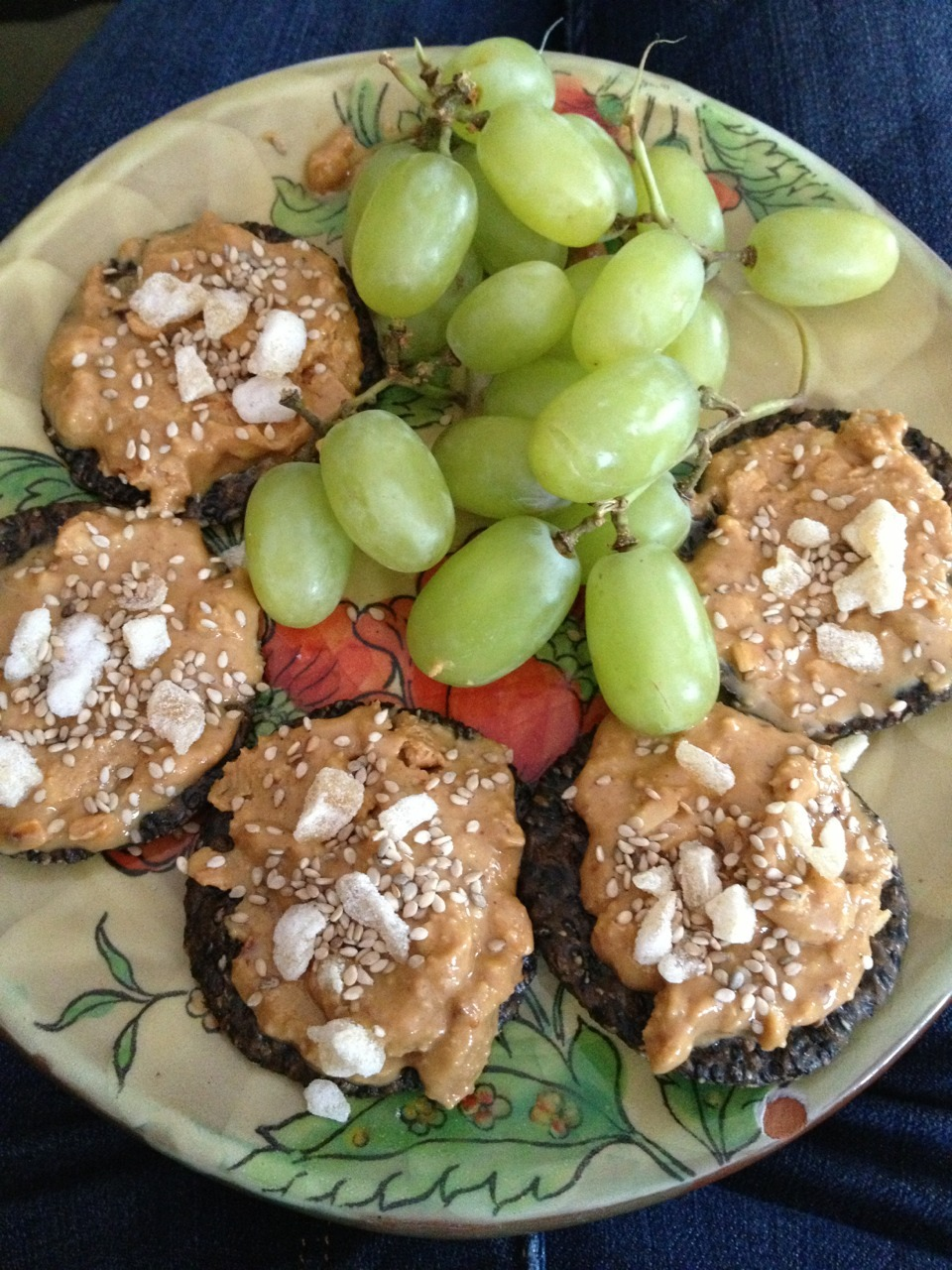 Black rice cracker with peanut butter sesame seeds and ginger chips! Green grapes holla