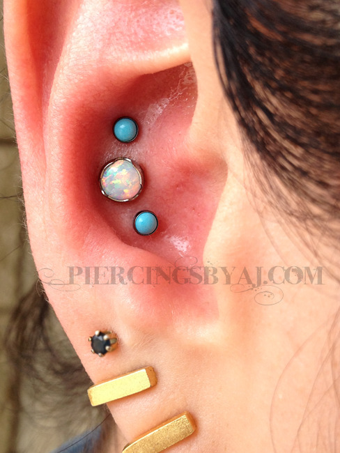 piercingsbyaj:  Fresh triple conch. 14g 5mm prong set white opal center piece from Anatometal with two 18g 3mm bezel set turquoise gems from Neometal.