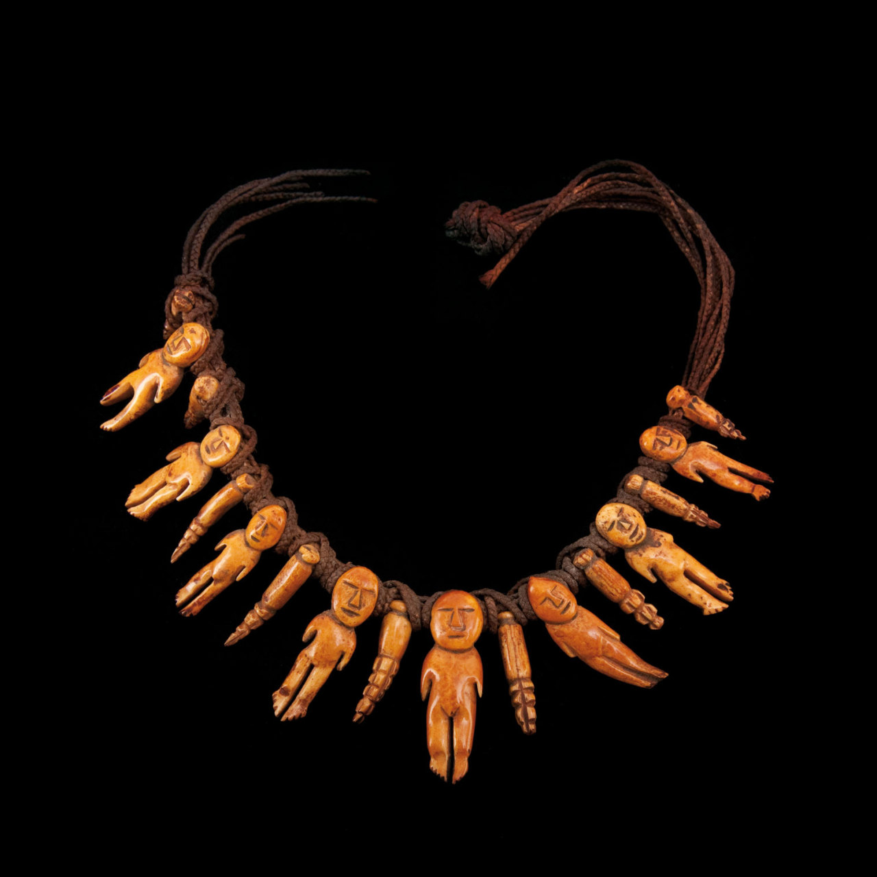 Tongan necklace, the figurative composition of this adornment is extremely rare, it carries eight figures and nine other pendants, all pierced for suspension and bound by sennit cord. This Oceanic work of art, crafted from bone for a person of high standing. Believed to be female goddess effigies, these sacred figurines have at times been accorded to high ranking Tongan women such as the Mehekitanga, an important family relation in Tongan culture, or the Tamaha, the niece to the King of Tonga through his sister.