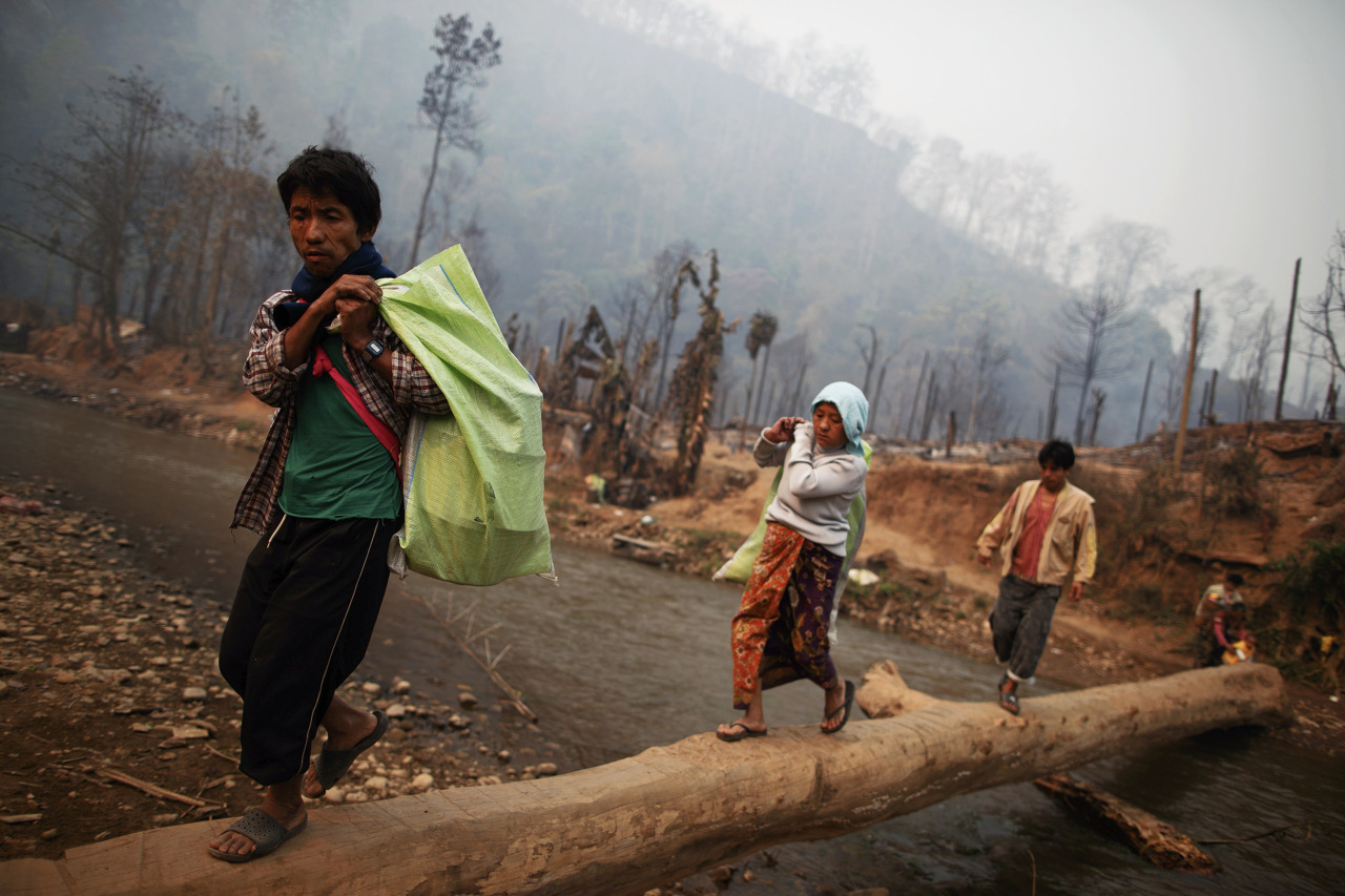 Top pictures from the past 24 hours: in this picture, survivors carry aid and belongings from the ruins of a refugee camp. At least 42 people died in a fire at a camp which is home to thousands of refugees from Myanmar, near the Thai-Myanmar border on Friday, local media reported.