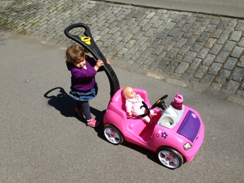 Chloe pushing her baby in a car.