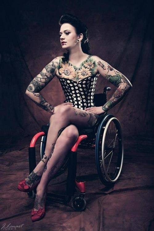 goodbodiesareallbodies:  [ photo is a person with multiple tattoos, wearing red shoes and a black and white polka dot corset. she is sitting in a wheelchair and has her hands on her hips, looking off to the side. ]
