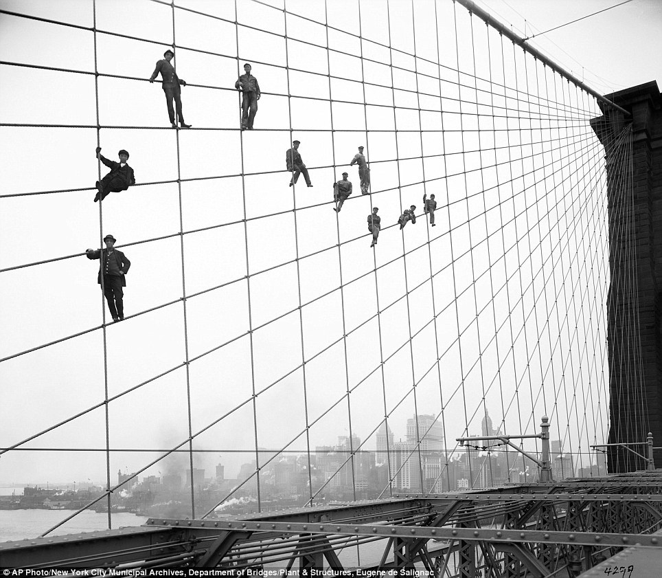 Painters hang from suspended wires on the Brooklyn Bridge October 7, 1914. Via.