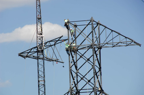 Linemen build 300 foot tall transmission towers on a hillside adjacent to Grand Coulee Dam. The towers will support new high voltage transmission lines linking Grand Coulee's Third Powerplant with a switchyard one mile away. The lines span 3600 feet across the Columbia River.