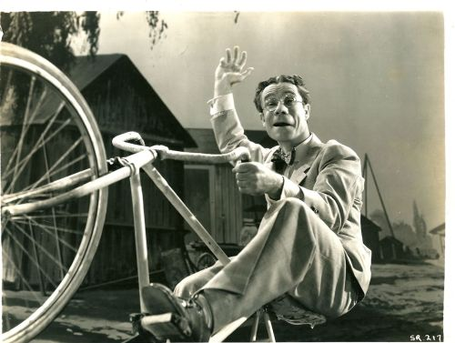 Joe E. Brown rides a bike. Wheelie-n'.
